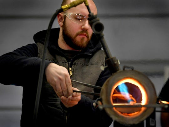 Alex McCormick of Bonner, Montana, reaches into a forge