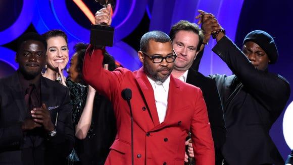 Jordan Peele accepts the best feature award, after