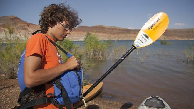 Gabe Ennis demonstrates the use of proper safety equipment for kayaking at Quail Creek Reservoir on Wednesday, June 24, 2015.
