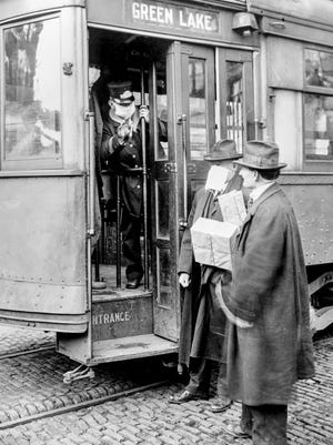 Businessmen make different choices about wearing masks to help protect themselves from the Spanish flu in Seattle in 1918.