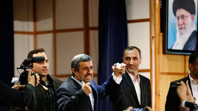 Former Iranian President Mahmoud Ahmadinejad (center), next to a picture of Iranian Supreme leader Ayatollah Ali Khamenei, as he is surrounded by media after registering his candidacy at the Ministry of Interior in Tehran, Iran, April 12, 2017, for Iran's upcoming presidential elections on May 19.