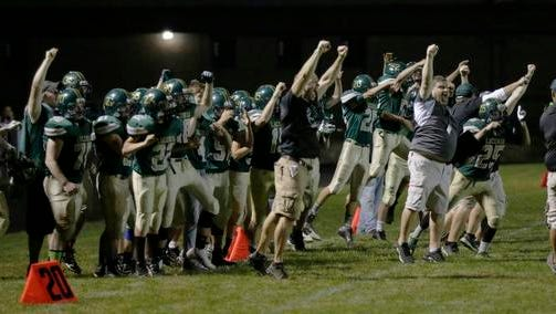 Laconia coaches and players jump as they defeat Winnebago Lutheran 26-20 in double overtime.