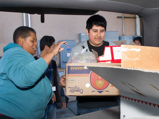 Jeanette Shorter, left, with Morningstar Church, directs Erik Lopez, a student at the New America School, to load food into her vehicle at the Las Cruces Gospel Rescue Mission Monday morning as part of a service project on Martin Luther King Jr. Day.