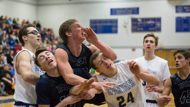 Yale and Imlay City players get tied up as they go for a rebound during a basketball game Friday, Feb. 12, 2016 at Imlay City High School.