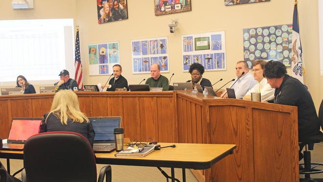 From left to right: Iowa City Community School Board members Lori Roetlin, Phil Hemingway, Brian Kirschling, Chris Lynch, LaTasha DeLoach, Paul Roesler and Chris Liebig discuss plans for an upcoming bond issue alongside recording secretary Kim Colvin on Jan. 31, 2017.