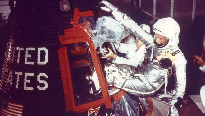 """Overall view of Astronaut John Glenn as he enters into the spacecraft """"Friendship 7"""" prior to MA-6 launch operations at Launch Complex 14. The story is that Glenn asked his children for suggestions on what to name his ship. He added """"7,"""" in honor of his Mercury Project astronauts."""
