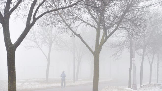 A runner gradually fades into the thick fog during a jog around Whitney Park.