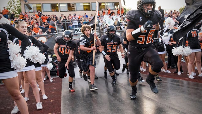 The Marine City Mariners charge through the tunnel at the start of the game against Marine City Sept. 15.