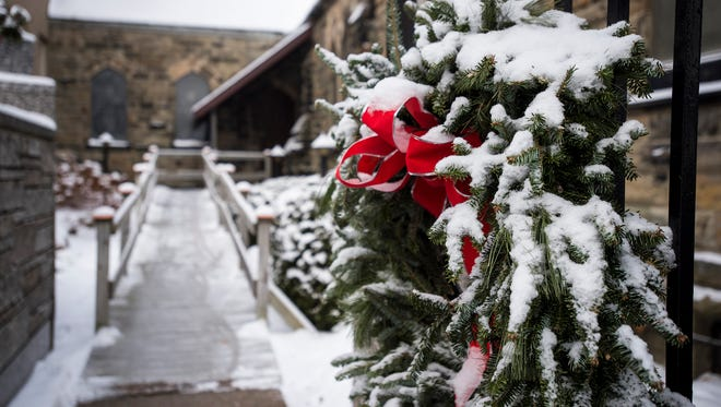 A thin layer of snow covers a wreath that hangs on a gate at the Grace Episcopal Church in Port Huron.