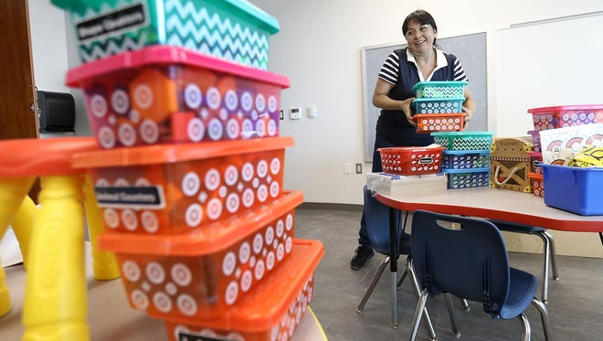 FILE - An elementary school teacher gets her classroom ready for students.