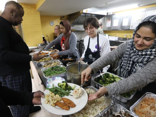 Amber Huq, of Paterson, serves Christmas dinner at
