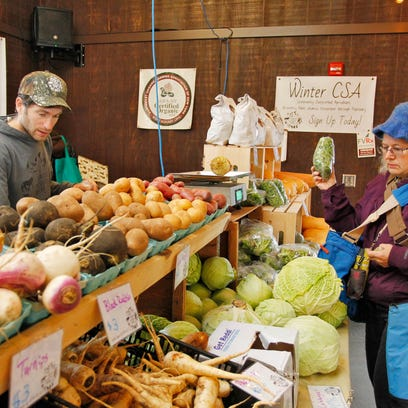 Bret Morris of Shared Roots Farms helps Heather Kirkland