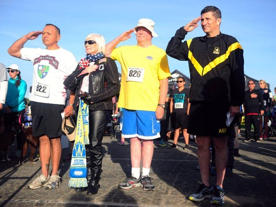 Runners salute before participating in a past Honor Our Fallen Run at Ft. Ord.