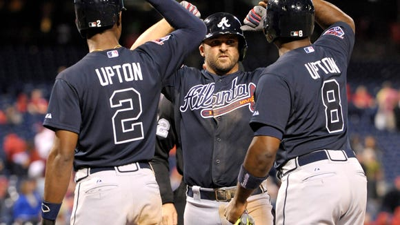 Braves second baseman Dan Uggla celebrates his grand slam home run with teammates B.J. Upton (2) and Justin Upton in the ninth inning Monday in Philadelphia.