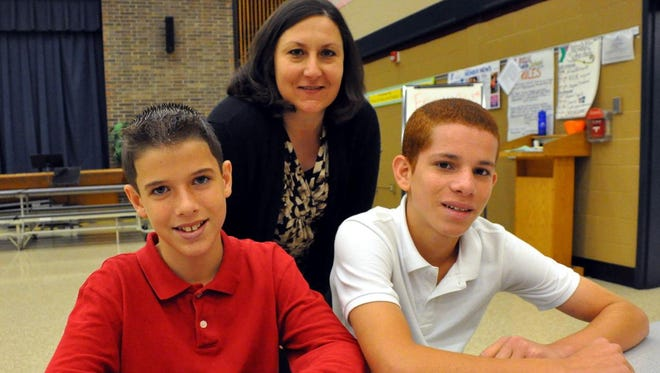 Henry Garton (left) and Juan Correa Santiago, students at Rossi Middle School in Vineland , are pictured with Principal Tammy Monahan, school principal. Henry was recognized for helping Juan.