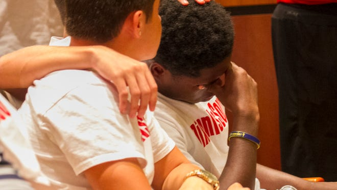 Thomas Edison is consoled by his teammates after speaking on behalf of his football coach Anthony Dixon at the Lee County School Board meeting on Tuesday, Aug. 23, 2016, in Fort Myers.