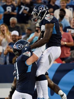 Titans offensive tackle Dennis Kelly (71) celebrates with wide receiver Taywan Taylor (13) after his touchdown during a preseason game against the Buccaneers at Nissan Stadium Saturday, Aug. 18, 2018, in Nashville, Tenn.