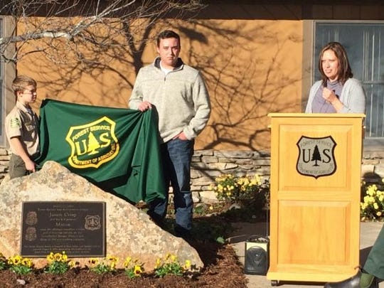 Logan, Garrett and Amanda Crisp unveil the Memorial Stone in honor of their father and husband Officer Crisp at  a dedication  renaming the Forest Service Ranger Station.