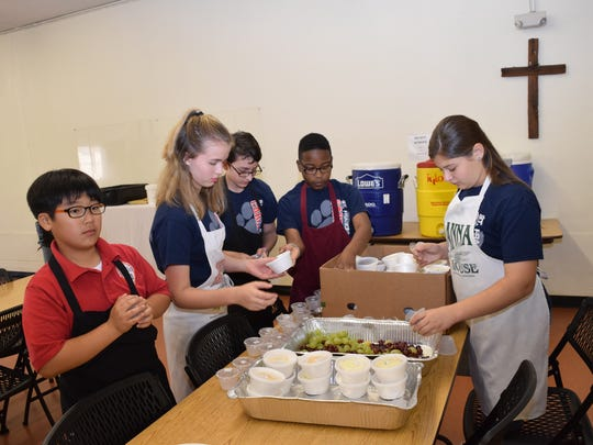 Chris Noh (far left), Emma Shear, Kenterrus Coleman and Nicole Evans, all sixth-graders at St. Frances Cabrini School, were among the 15 students who were doing community service at the Manna House for Lent on Friday.