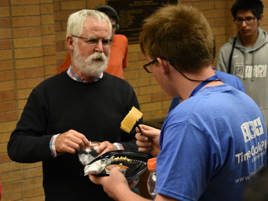 William Wolfe, the director of ASU Code Camp, talks with a camper wearing one of the shirts TimeClock Plus supplied on June 8, 2018 in the hallway at Angelo State University.
