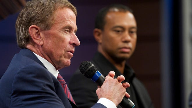 In a file photo from March 2014, PGA Tour commissioner Tim Finchem answers questions next to Tiger Woods during a news conference at Congressional Country Club in Bethesda, MD.