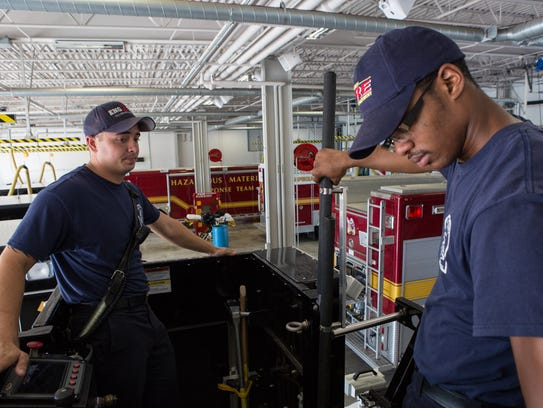 Firefighter EMT, Landon Ross, left, converses with