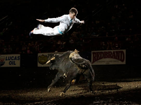 Bull jumper Manu Lataste leaps over a bull in the center