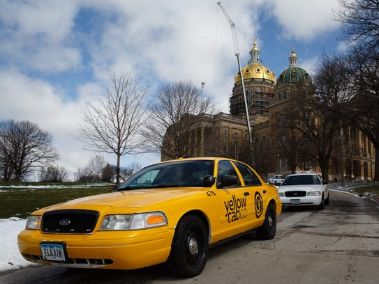 A line of taxis leaves the Iowa Capitol after a rally