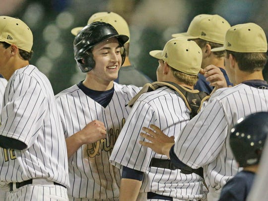 Cathedral's Jared Poland, center, is congratulated by teammates after scoring during the City Championship Game against Heritage Christian at Victory Field, May 13, 2016.