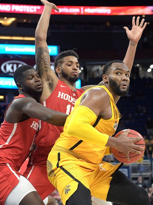 Wichita State center Shaquille Morris (24) posts up for a shot in front of Houston forward Nura Zanna, left, and forward Devin Davis (15) during the second half of an NCAA college basketball game in the semifinals of the American Athletic Conference tournament Saturday, March 10, 2018, in Orlando, Fla.  Houston won 77-74. (AP Photo/Phelan M. Ebenhack)
