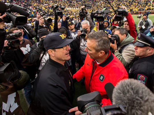 Michigan head coach Jim Harbaugh, center left, shakes hands with Ohio State head coach Urban Meyer, center right, after an NCAA college football game in Ann Arbor, Mich., Saturday, Nov. 25, 2017. Ohio State won 31-20. (AP Photo/Tony Ding)