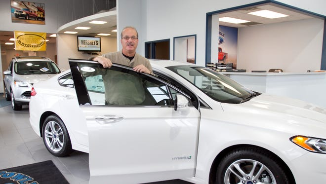 Ken Hagar, owner of Fowlerville Ford, stands in the showroom next to a 2016 Fusion Hybrid.