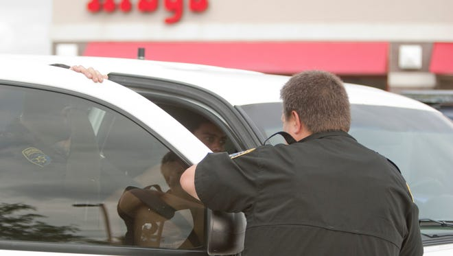 Livingston County sheriff's deputies talk to a Lansing man they believe fled police after an alleged retail fraud attempt at the Tommy Hilfiger store at the Tanger Outlet Mall in Howell Township. Police said the man ditched a shirt while fleeing from the Arby's parking lot on Burkhart Road and across all lanes of Interstate 96 around 4:50 p.m. Friday.