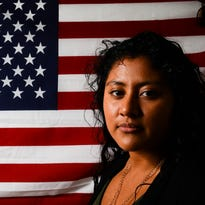 Viviana Alamillo, 22, stands in front of a large American flag that hangs on a wall in her bedroom Wednesday, Oct. 12, 2016, in Lansing. Alamillo immigrated from Mexico to the U.S. at the age of 3 and lived illegally in the U.S. for more than 15 years before gaining DACA status. She has since interned at the state House and the U.S. House of Representatives. She is the first in her family to go to college.