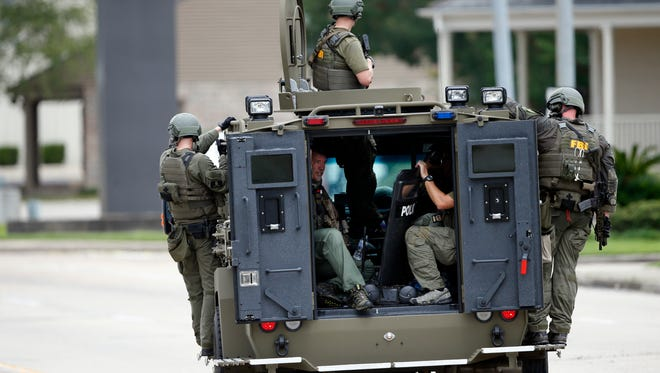 FBI patrol the perimeter of the crime scene in an armored vehicle where Baton Rouge police were shot, in Baton Rouge, La., on July 17, 2016.