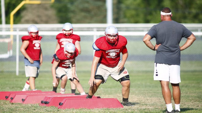 Former Loudonville football coach Kevin Maltarich (right) watches his players run drills during a practice.