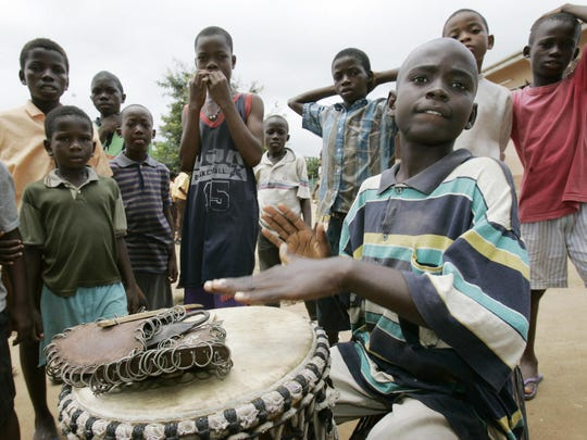 Liberian refugee children pose as one plays a drum at the Buduburam Refugee Camp in 2005.