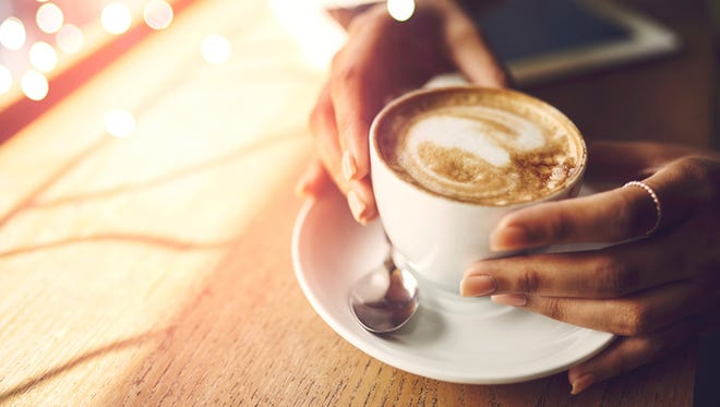 Closeup shot of an unrecognizable woman having a cup of coffee at a cafe