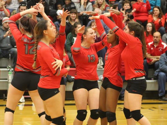 Livonia Clarenceville's volleyball team celebrates a point in Tuesday's Class B regional tournament.
