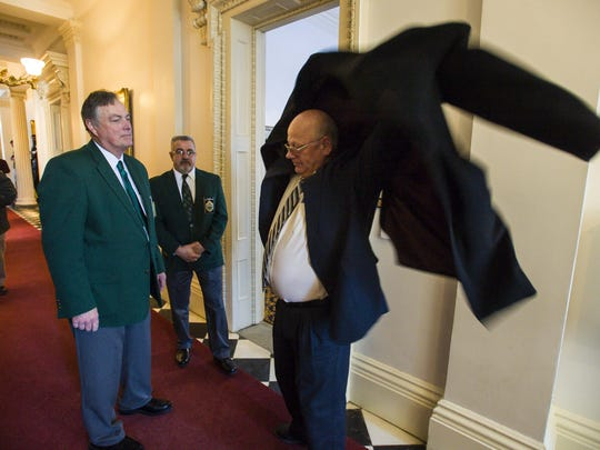 Sen. Norm McAllister, R-Franklin, dons his coat before leaving the Statehouse after being suspended from the Senate in Montpelier on Wednesday, January 6, 2016.