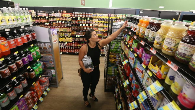 Allie Pierce, Rochester, stops to shop for a few items on her way to work in Victor at the Railside Market and Cafe in Victor Wednesday, July 12, 2017.
