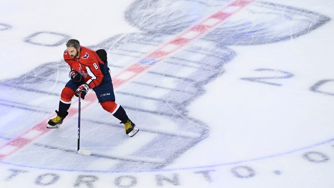 Washington Capitals left wing Alex Ovechkin (8) skates over the Stanley Cup logo in warm up before playing against the Carolina Hurricanes in an exhibition NHL hockey game Wednesday, July 29, 2020 in Toronto.