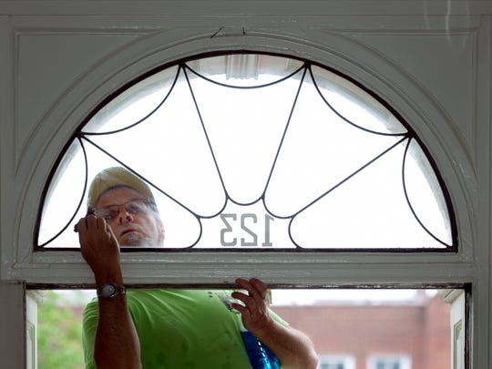 Architectural designer and volunteer Terrence Downs of North York cleans the transom window over the front door of the Goodridge Freedom House Friday, May 12, 2016. Workers are preparing the house and Underground Railroad museum for its grand opening May 21 from 1 p.m. to 5 p.m. Bill Kalina photo