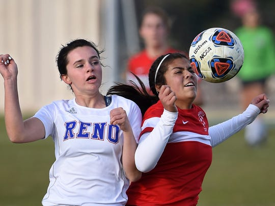 Reno's Shelby Clayton, left, and Wooster's Joanna Antelo battle for the ball during Tuesday regional game at Reno High School on Tuesday.