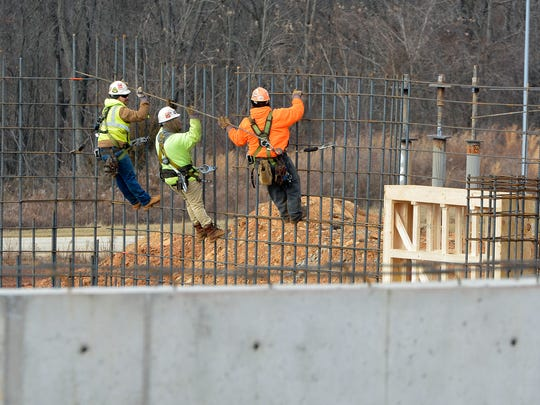 Iron workers build the wall framework as construction