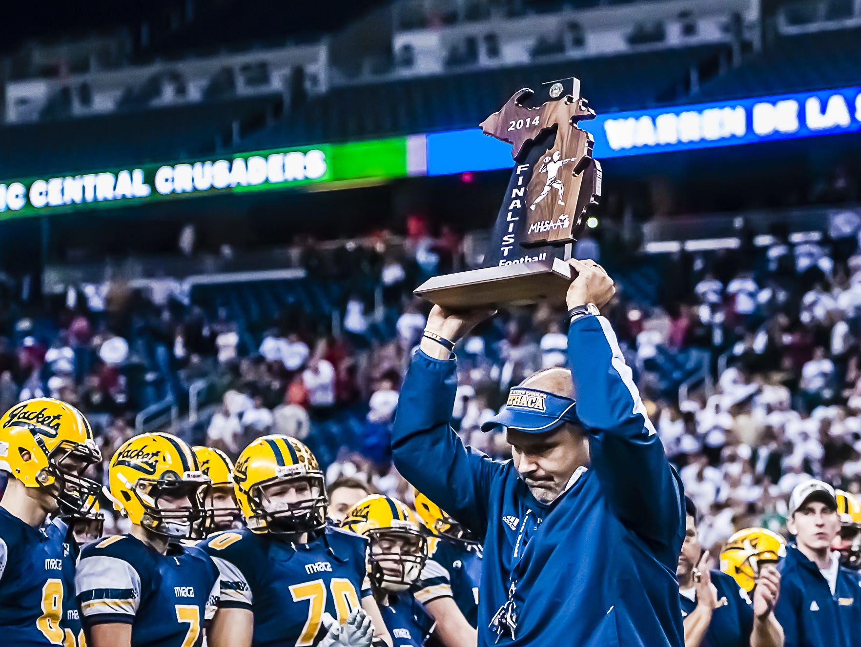Ithaca Head Football Coach Terry Hessbrook displays the runner-up trophy after their Division 6 state championship loss to Monroe St. Mary Catholic Central Friday Nov. 28, 2014 at Ford Field in Detroit.