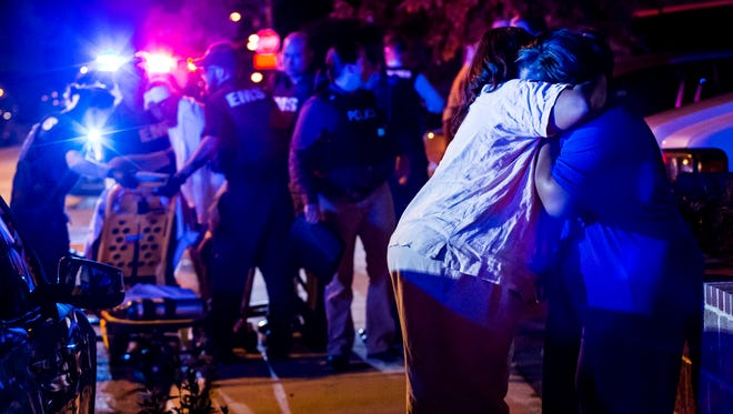 A woman is comforted by another as a man who was injured in a shooting is helped onto a stretcher by paramedics at the scene in the 500 block of W. 31st St. on Monday night.