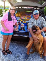 Gail Cochran, left, husband Mike and their dog Gypsy Sue welcome guests to Island Gypsy Marina Bar's 5th annual birthday party that raised 2,600 pounds of food for the Humane Society of Naples.