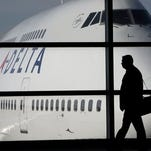 In this file photo made Jan. 21, 2010, a passenger walks past a Delta Airlines 747 aircraft in McNamara Terminal at Detroit Metropolitan Wayne County Airport in Romulus, Mich. Delta Air Lines on Tuesday, July 22, 2014 canceled all flights to Israel until further notice, citing reports that a rocket landed near Tel Aviv's Ben Gurion Airport. (AP Photo/Paul Sancya, File)