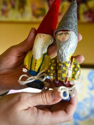 Zoe Back holds two of her decorated and dressed gnomes.